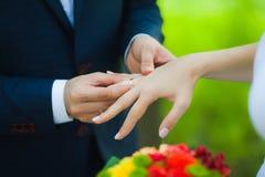 Plan rapproché des mains des ajouter méconnaissables nuptiales aux anneaux de mariage la jeune mariée tient le bouquet de mariage Image stock