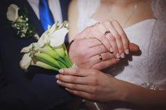 Plan rapproché des mains des ajouter nuptiales aux anneaux de mariage La jeune mariée tient le bouquet de mariage des fleurs blan Photographie stock