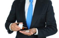 Pilules de versement d'homme d'affaires dans sa main Photographie stock libre de droits
