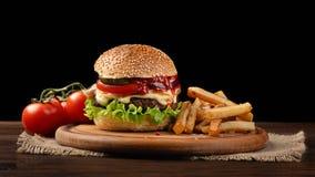 Plan rapproch? fait maison d'hamburger avec du boeuf, la tomate, la laitue, le fromage et les pommes frites sur la planche ? d?co photo libre de droits