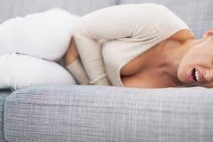 Plan rapproché sur sentir la mauvaise jeune femme s'étendre sur le sofa Image stock