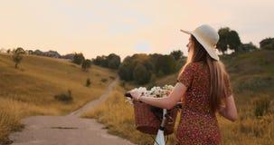 Plan trasero: Rubio hermoso en el vestido y la bici retra que caminan en el camino en el campo del verano almacen de video
