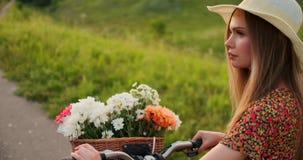 Plan trasero: Rubio hermoso en el vestido y la bici retra que caminan en el camino en el campo del verano almacen de metraje de vídeo
