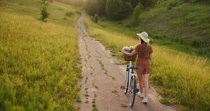 Plan trasero: Rubio hermoso en el vestido y la bici retra que caminan en el camino en el campo del verano metrajes