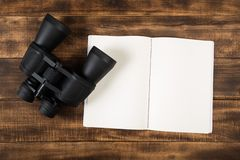 Plan for traveling, binoculars on wooden floor with notebook royalty free stock photography