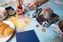 Plan of trip. Background - what to take for a trip. Women`s hands and map, retro camera, money, coins, croissant, coffee, pen, compass, sunglasses Stock Photography