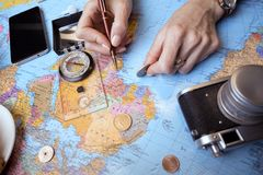 Plan of trip. Background - Women`s hands and map, retro camera, money, compass Stock Images