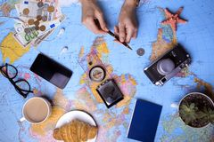 Plan of trip. Background - Women`s hands and map, retro camera, money, compass Stock Image