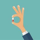 Plan vektorillustration av handen som rymmer preventivpilleren Arkivfoto