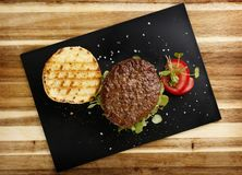 Plan view of a succulent and juicy rare beef burger, with tomato and watercress garnish, in a bread bun. On a slate plate stock photos