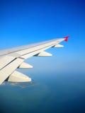 Plan vinge i en blå himmel ovanför den tropiska ön Arkivbild