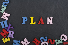PLAN word on black board background composed from colorful abc alphabet block wooden letters, copy space for ad text royalty free stock image