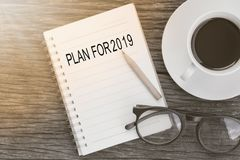 Plan for 2019 word on notebook with glasses, pencil and coffee cup on wooden table. Business concept.  royalty free stock photos