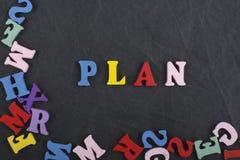 PLAN-Wort auf dem schwarzen Bretthintergrund verfasst von den hölzernen Buchstaben des bunten ABC-Alphabetblockes, Kopienraum für Lizenzfreies Stockbild