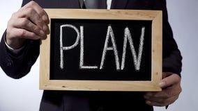 Plan written on blackboard, businessman holding sign, business concept, strategy Stock Photos