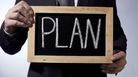 Plan written on blackboard, businessman holding sign, business concept, strategy Royalty Free Stock Photo