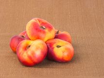 Plana persikor (munkpersikor) på en bakgrund Royaltyfria Foton