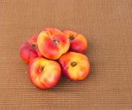 Plana persikor (munkpersikor) på en bakgrund Arkivbild