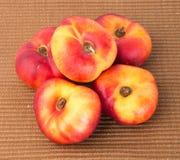 Plana persikor (munkpersikor) på en bakgrund Fotografering för Bildbyråer