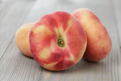 Plana persikor på den wood tabellen Arkivfoto