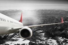 Plana röda svarta vita berg för lopptransportionflygplan Arkivbild