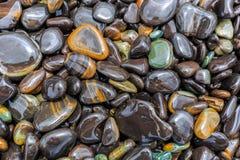 Plana skinande stenar på stranden Royaltyfria Bilder
