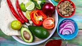 Plana tortillor och olika grönsaker för taco eller burritoen som gör på lantlig bakgrund, bästa sikt, mexicanskt laga mat recept  arkivfoto