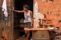 Planaltina,戈亚斯,巴西4月21日2018年:年轻女人站立她的Planaltina的贫困社区的,布拉吉家外 免版税库存照片