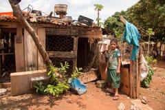 Planaltina, Goias, Brésil 27 octobre 2018 : Un jeune garçon se tenant prêt une cage de poulet en dehors de sa maison dans la pauv images stock