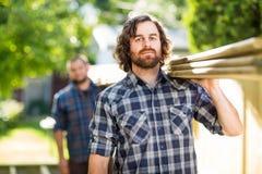 Plance di legno di With Coworker Carrying del carpentiere Immagine Stock