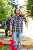 Plance di legno di And Coworker Carrying del carpentiere a Immagini Stock