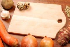 Planche à découper avec des légumes image stock