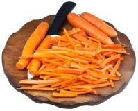 Planche à découper avec la carotte coupée en tranches et le couteau en céramique Photo stock