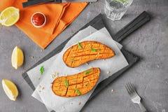 Planche à découper avec la patate douce cuite au four image stock