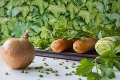 Planche à découper avec les carottes, le céleri, le persil et l'union images libres de droits