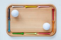 Planche à découper avec les tees de golf et les boules de golf en bois Photographie stock