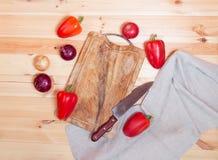 Planche à découper, couteau et légumes frais sur le fond en bois image stock