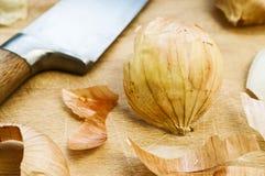 Planche à découper d'épluchages, de couteau et en bois d'oignon à l'arrière-plan Photographie stock libre de droits