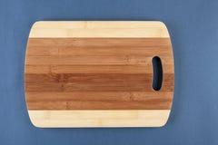 Planche à découper de cuisine sur un bleu Photographie stock