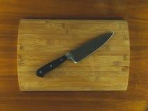 Planche à découper en bois avec un couteau diagonal image stock