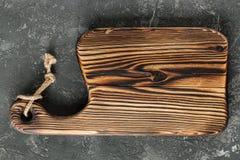 Planche à découper en bois sur le fond concret noir photo libre de droits