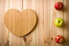 Planche à découper en forme de coeur avec des pommes Photo stock
