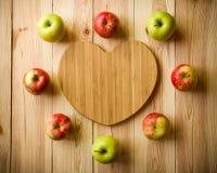 Planche à découper en forme de coeur avec des pommes Image stock