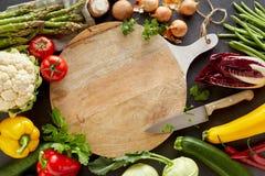 Planche à découper en gros plan parmi des légumes photographie stock libre de droits