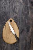 Planche à découper et couteau sur un bois Image libre de droits