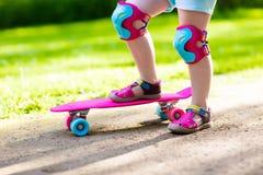 Planche à roulettes d'équitation d'enfant en parc d'été Images stock