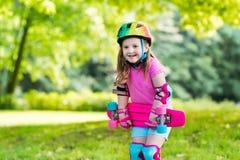 Planche à roulettes d'équitation d'enfant en parc d'été Photographie stock libre de droits