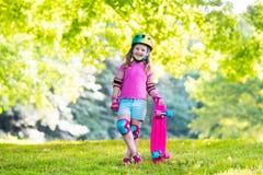 Planche à roulettes d'équitation d'enfant en parc d'été Image libre de droits