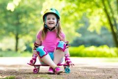 Planche à roulettes d'équitation d'enfant en parc d'été Photographie stock