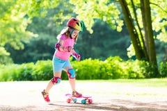 Planche à roulettes d'équitation d'enfant en parc d'été Image stock